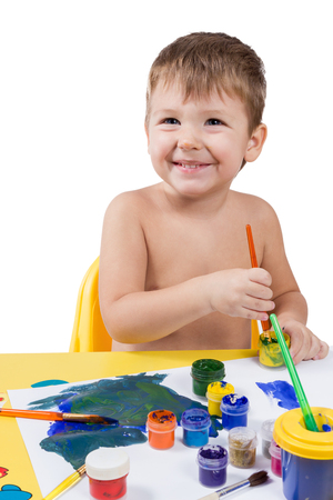 unclothed: Little boy sitting at a table with a brush and paints isolated on white background