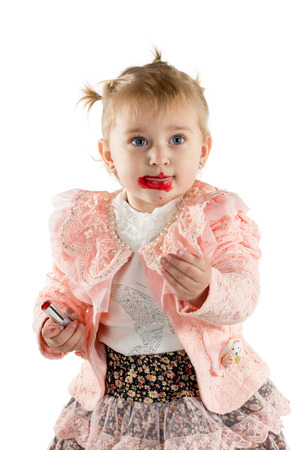 Little girl with lipstick smeared paints her lips yet isolated on a white background Stock Photo