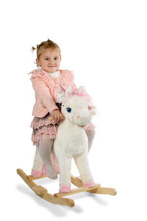 Little girl rides a toy horse rocking isolated on a white background photo