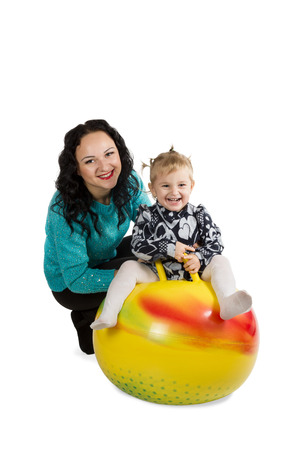Portrait of a mother and her daughter who is sitting on a big ball isolated on white background photo