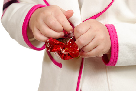 deliberation: Childrens hands deploy the red wrapper with chocolate candies closeup isolated on white background