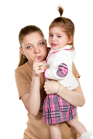 hysterics: Little daughter crying on his mother arms which indicates forefinger at the camera isolated on a white background Stock Photo