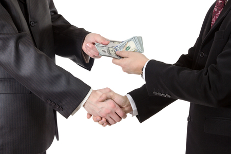Handshake with the transfer of money from one businessman to another closeup isolated on white background photo