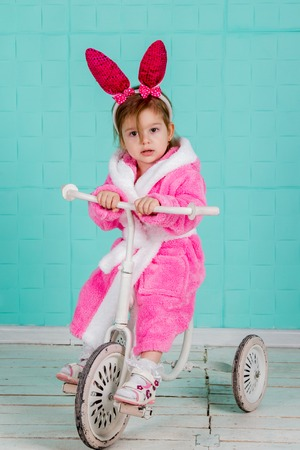 three year old: Little cute girl in pink rabbit costume sits on an old tricycle Stock Photo