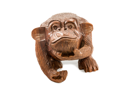 statuette: Small wooden statuette monkey chimpanzee staring up at the camera isolated on a white background Stock Photo