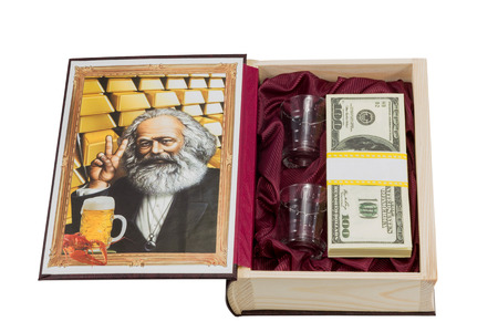Open casket in form of book with picture of Karl Marx and gold with two glasses and pack of dollars isolated on a white background photo