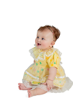 Portrait of little girl in a yellow dress sitting and looking sideways isolated on a white background photo