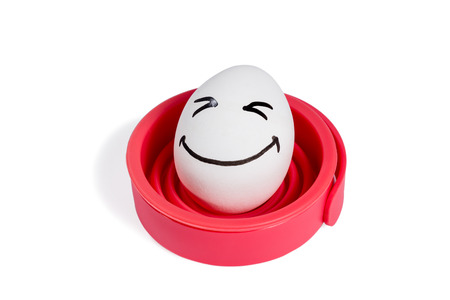 closed eyes: Egg with a painted smile and closed eyes on the red stand isolated on white background Stock Photo