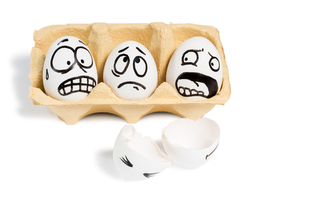 Three eggs with frightened faces looking at a broken egg lying near isolated on white background