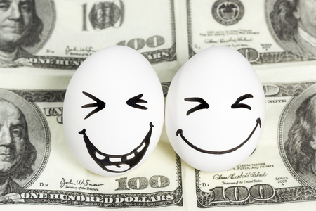 two dollar bill: Two eggs with painted faces laughing at the a hundred dollar bill Stock Photo