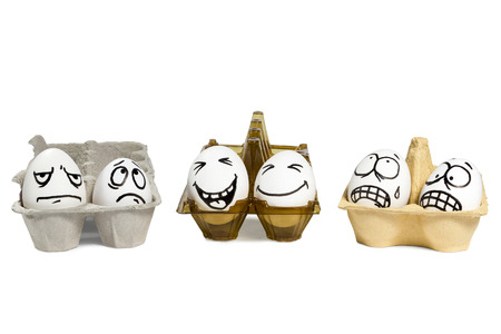 Two eggs with funny faces in a plastic tray, and next to them four eggs with angry faces in paper trays isolated on white background Standard-Bild
