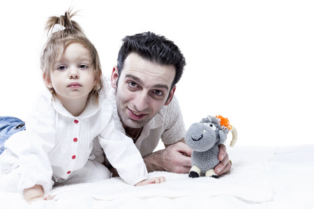 unshaven: Unshaven man lies and playing with baby girl holding soft toy looking at the camera