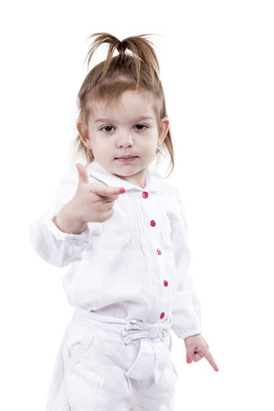 Portrait of a pretty little girl in a white suit with exposed index fingers on both hands isolated on a white background photo