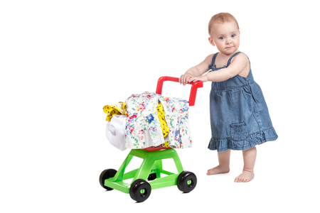 Little girl in denim dress driven child plastic shopping trolley full of clothes isolated on white background Banco de Imagens