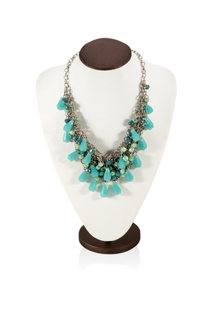 Beautiful necklace of turquoise stones on the metal chain on the bust for display isolated on a white background photo