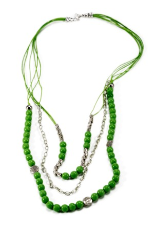 Necklace handmade with green beads metal ornamentation and chain isolated on a white background