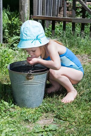 little girl swimsuit: Little girl in a blue swimsuit sat at metal buckets and drinking water from their hands