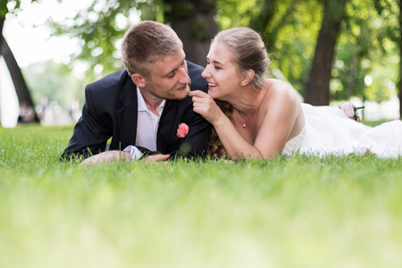caresses: Bride and groom lying on the grass facing the camera caresses groom and bride caresses groom a blade of grass on the nose Stock Photo