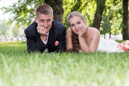 honeymooners: Retrato de un reci�n casados ??que mienten en la hierba y se inclina en la mano mirando a la c�mara