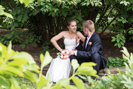wedding gawn: Peeping as the bride and groom are sitting on the curb in the park and argue with each other Stock Photo
