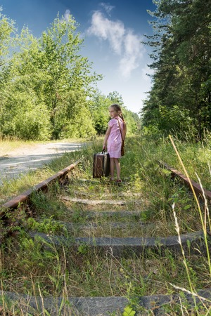 petite fille avec robe: Little girl in a pink dress with a suitcase goes by rail and turned back Banque d'images