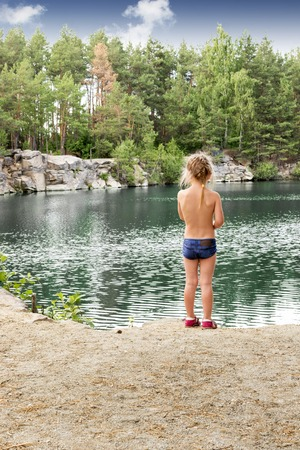 behind: Girl in a bathing suit standing with her back to the camera on the rocky shore of the lake