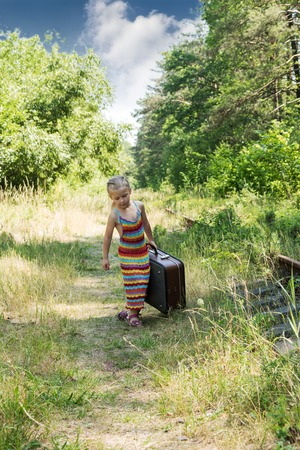 forest railway: Little girl in a dress bear a heavy suitcase along the railway in the forest Stock Photo