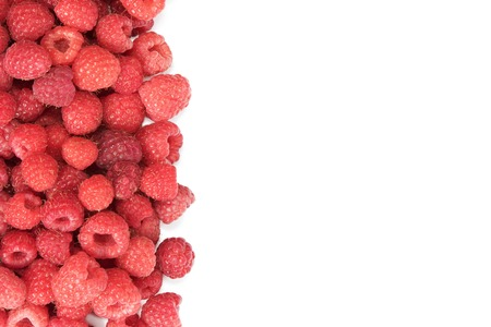 occupying: Pile of fresh raspberries occupying part of the picture with space for your text isolated on white background