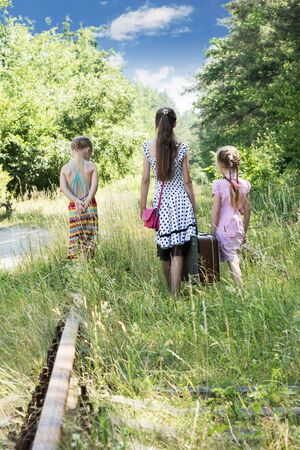 three sisters: Three sisters with a suitcase goes away by railway in the woods