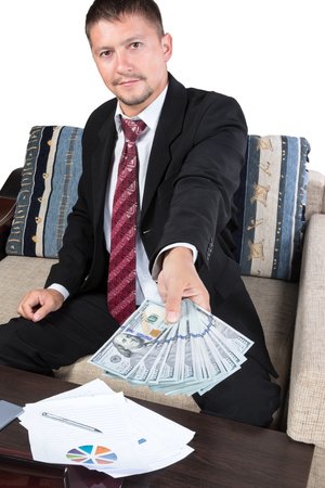 extends: Young businessman sitting at the table extends to the camera hundred-dollar bills arranged fanned out Stock Photo