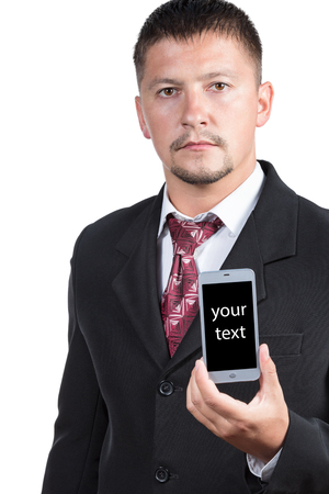 your text: A man with a beard and mustache, in a suit and tie to hold a smartphone in one hand with a black screen for your text isolated on white background Stock Photo