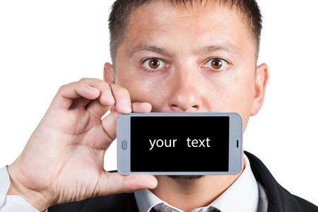 boca: Un hombre en un traje tiene un tel�fono inteligente en una mano con una pantalla en negro para el texto cerca de la boca aislado en fondo blanco
