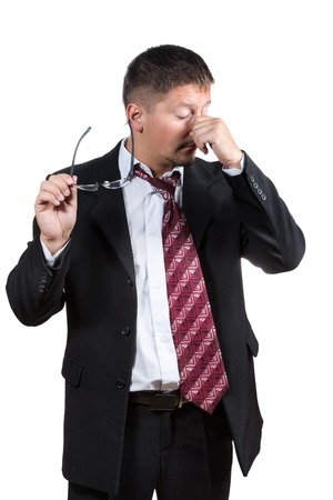 touching noses: Tired businessman closed his eyes and raised his glasses and rubs his nose isolated on white background Stock Photo