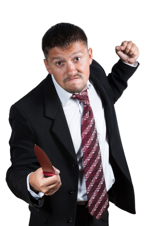 vindictive: Angry man in a suit, shirt and tie in one hand holding a red knife and the other clasped in a fist for strikes isolated on white background