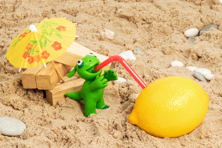sand lime bricks: Green plasticine animal sits near wooden blocks on the beach and drink juice through a straw from a lemon Stock Photo