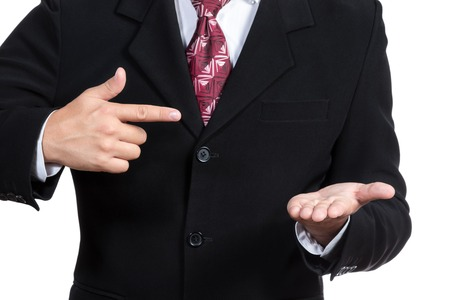 Man in a suit holding a hand palm up in front of the other points on the hand isolated on white background