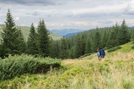 man standing alone: Mountain forest landscape with a tourist with a backpack in the foreground Stock Photo