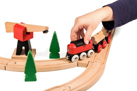 children hands: Child plays children wooden train isolated on white background
