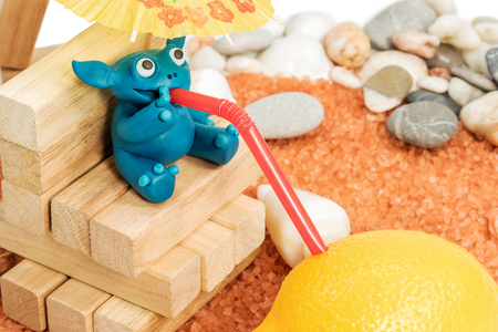 thin shell: Blue plasticine animal sits on wooden blocks on the beach and drink juice through a straw from a lemon