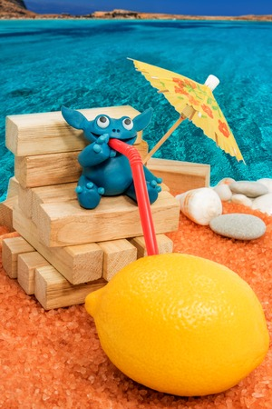 sand lime bricks: Blue plasticine beast drinking juice straight from the lemon on the beach by the sea