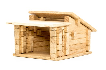 without windows: Small toy house made of wood blocks and without windows doors close-up isolated on white background