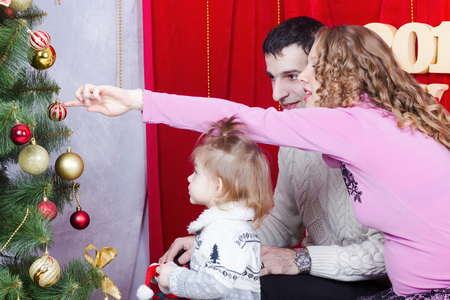 decorar: Pregnant mother, father and daughter decorate a Christmas tree