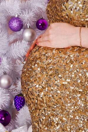 Pregnant belly with hands on him on the background of the Christmas tree closeup