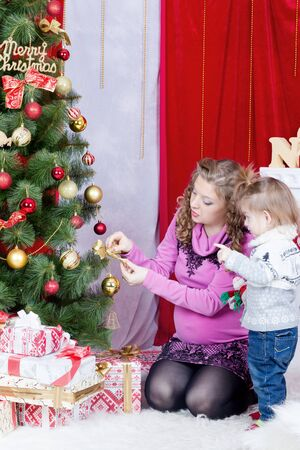 se cramponner: Mother and daughter cling together on Christmas tree decoration