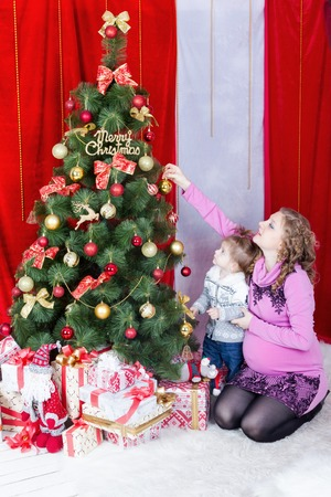 se cramponner: Mom and daughter cling together on Christmas tree decoration