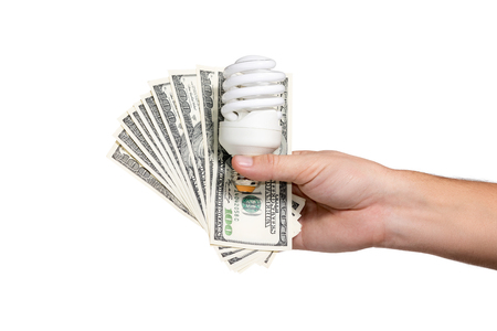 Male hand holding a fan of hundred-dollar bills, and energy-saving light bulb