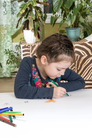 felt tip pen: Girl intently draws on a large white sheet of felt tip pen