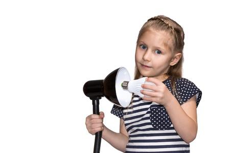 luminaire: Little girl twists LED lamp into the luminaire closeup isolated on white background Stock Photo