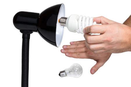 abandoning: Hand twists saving bulb in black lighting abandoning incandescent lamps isolated on a white background