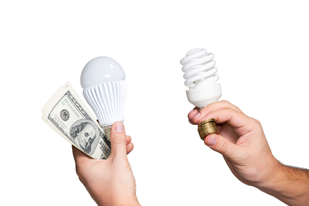 pack of dollars: LED lamp and a pack of dollars in one hand, and energy-saving lamp and a stack of coins in the other hand isolated on white background Stock Photo